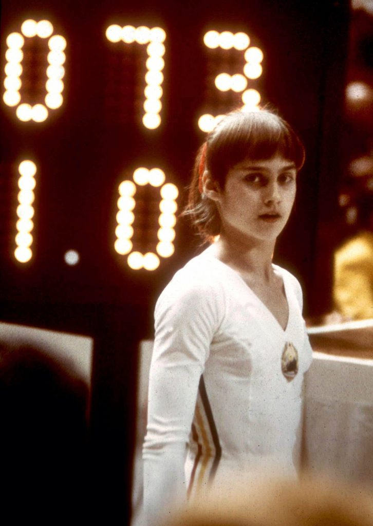 FILE - In this 1976, file photo, Romanian gymnast Nadia Comaneci stands before a scoreboard in Montreal, Canada. The Perfect 10 made the Romanian superstar more than a champion. It made her a legend. Yet four decades after her barrier-shattering uneven bars routine in Montreal, the one that ended with Comaneci and coach Bela Karolyi initially staring at the scoreboard in confusion when it read 1.00 because it wasn't outfitted to put up the first 10.0 in Olympic history, Comaneci wonders where the recognition of flawlessness has gone. (AP Photo/File)